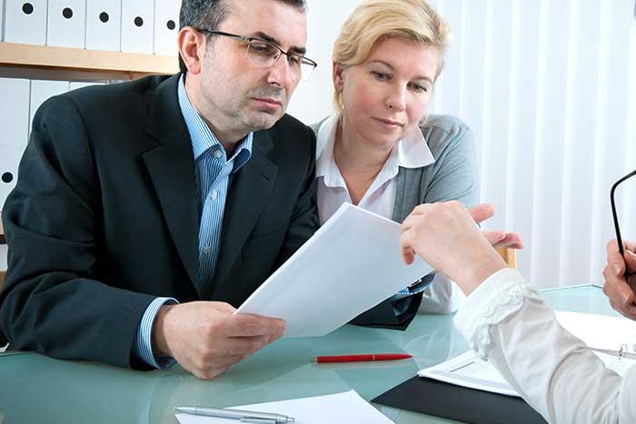 עורך דין לגירושין כשזוג מביט בחוזה