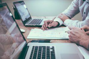 עורך דין גירושין בראשון לציון חישובי ממון עם שני מחשבים ניידים דף ועטים