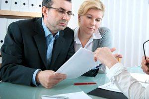 זוג יושב מול מסמך אצל עורך דין לענייני גירושין בחולון